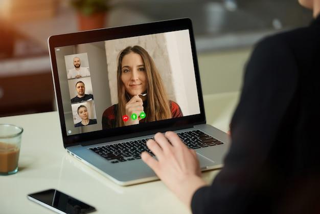 女性の肩越しのラップトップスクリーンビュー。