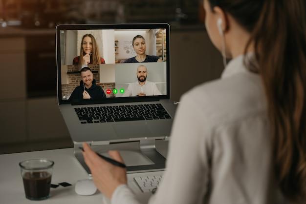 オンライン会議中に同僚とビデオ会議でリモートで作業している女性の背面図。ビデオ通話のパートナー。