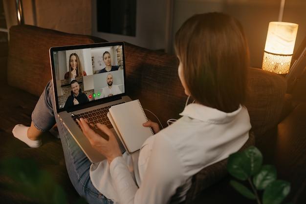 ノートパソコンでビデオ通話で同僚と話しているソファーに家で横になっている女性の背面図。ビデオ会議中にノートにメモをしている実業家。オンライン会議を行っているチーム