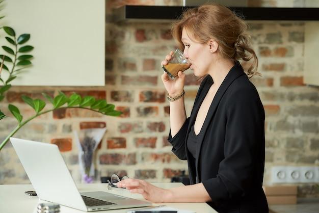 台所のラップトップでリモートで作業して幸せな女。自宅で同僚とビデオ会議中にコーヒーを飲む女性。オンライン講義の準備中に飲み物を飲む教師