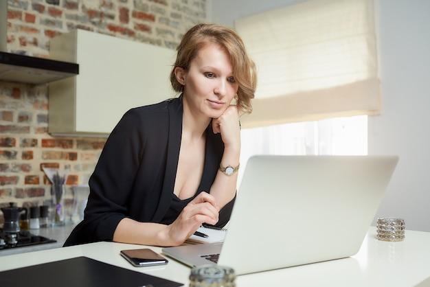 若い女性がキッチンのラップトップでリモートで作業します。自宅のビデオ会議で同僚の報告を落ち着いて聞いている美しい少女。オンライン講義の準備をしている女性教師