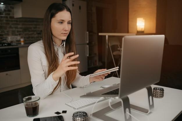 リモート作業。彼女のラップトップでオンラインでリモートで作業するヘッドフォンを持つブルネットの女性。居心地の良い自宅でのビデオ通話を通じて、同僚と積極的に問題について話し合っている少女。