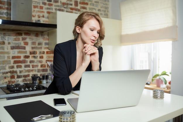 若い女性がキッチンのラップトップでリモートで作業します。自宅のビデオ会議で同僚の報告を話し合う魅力的な女の子。オンライン講義の準備をしている女教師。