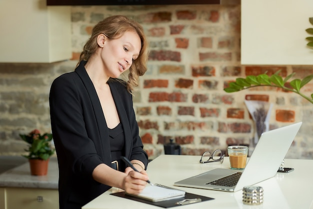 若い女性が彼女のキッチンで遠隔で働いています。彼女の従業員が自宅でビデオ会議で対処している間にノートにメモを書いている女性の上司。オンライン講義の準備をしている女教師。