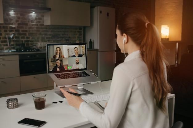 自宅のデスクトップコンピューターでのビデオ会議で、ビジネスについて同僚とリモートで話している女性従業員の背面図。オンライン会議の多民族のビジネスチーム。