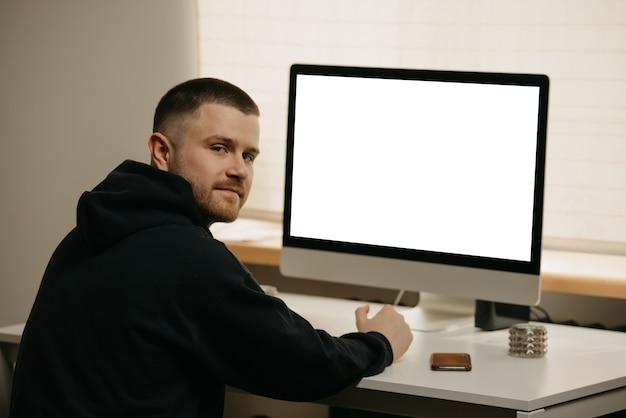リモート作業。ビジネスマンは、オールインワンコンピューターを使用してリモートで作業します。在宅勤務の優しい仲間。