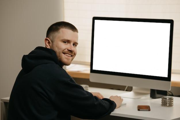 リモート作業。ビジネスマンは、オールインワンコンピューターを使用してリモートで作業します。在宅勤務の笑顔の仲間。