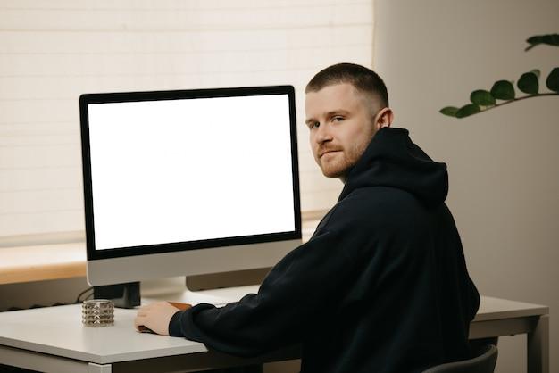リモート作業。ビジネスマンは、大型のオールインワンコンピューターを使用してリモートで作業します。在宅勤務の名誉ある仲間。