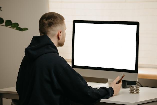 リモート作業。ビジネスマンの背面図は、オールインワンコンピューターを使用してリモートで動作します。自宅からスマホを持って仕事をしている仲間。