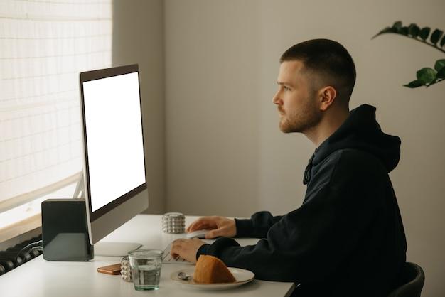 オンラインでリモート作業。プログラマーはオールインワンコンピューターを使用してリモートで作業します。仲間は家で熱心に働きます。