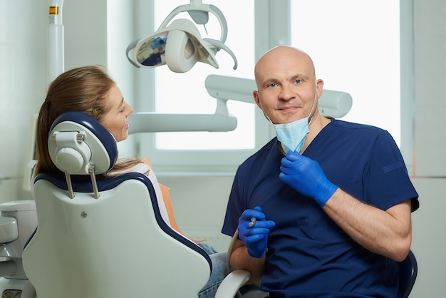 Стоматолог в униформе и одноразовые медицинские перчатки с пациентом в кабинете стоматолога