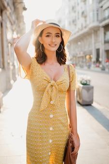 Милая молодая женщина в желтом платье с глубоким декольте держит шляпу на голове на закате в испании