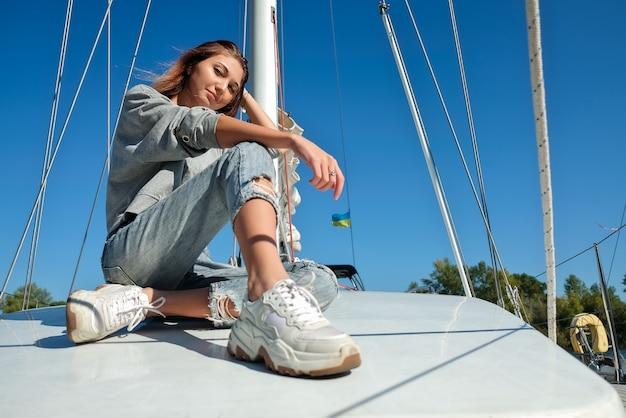 Красивая молодая женщина позирует на яхте.