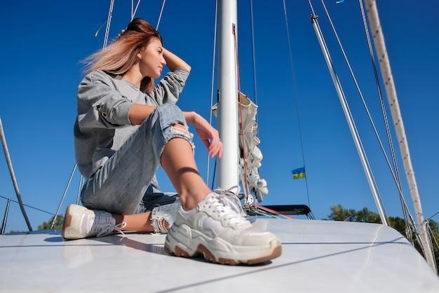 美しい若い女性がヨットでポーズします。