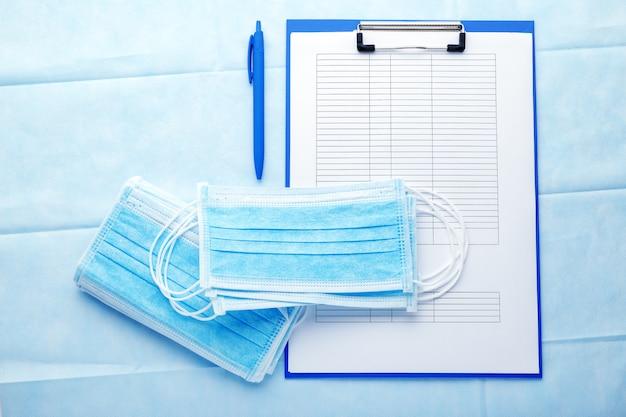 Назначение врача. медицинский тест формирует документы и медицинские маски, маски хирургической защиты на синем фоне.