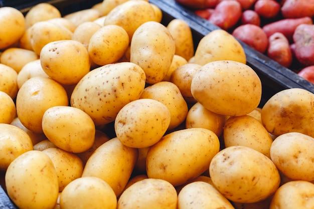 ファーマーズマーケットでの販売のための新鮮な生の有機生調理ジャガイモ野菜。ビーガンフードと健康的な栄養の概念。
