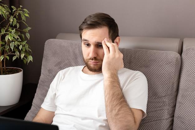 ノートパソコンとインターネットを使用してホームオフィスから働くストレスでストレス白人悲観的な男。リモート作業、ソファの上のフリーランサーのホームオフィスの作業場所。残業のバーンアウト