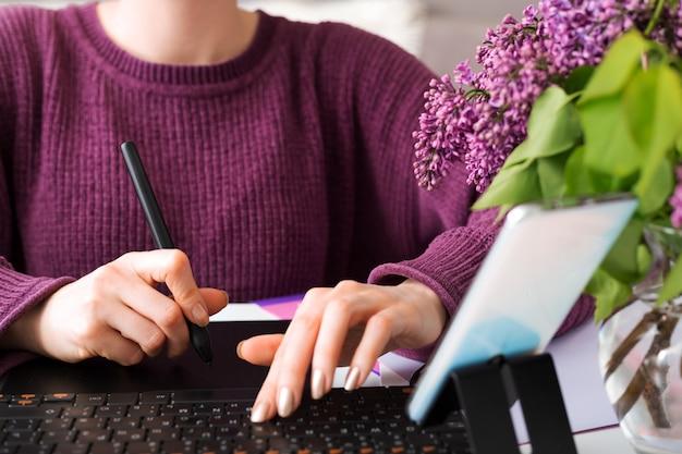 グラフィックデザイナーのレタッチャーフリーランサーは自宅で動作します。女性は、ラップトップ、コンピューターを使用して居心地の良いホームオフィスでグラフィックタブレットを描画します。リモート作業。ブロガーが電話を使用してオンライン放送のチュートリアルを記録