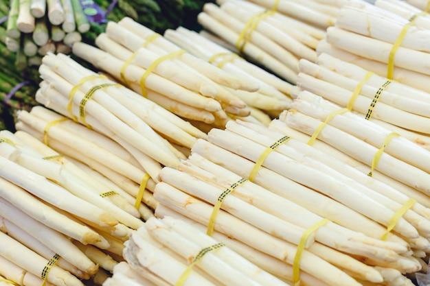 Пуки свежих сырцовых белых органических овощей спаржи для продажи на рынке фермеров. веганская еда и здоровое питание.