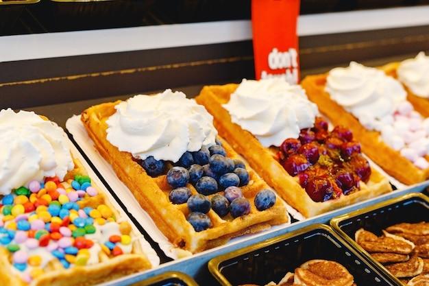 さまざまなトッピング、果物、お菓子、ホイップクリームのベルギーワッフルの屋台の食べ物。ベリー、チョコレートのワッフルデザート