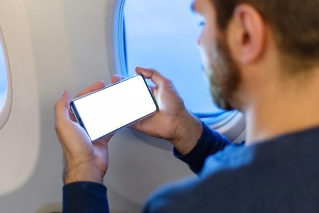 Кавказский человек, держащий пустой макет экрана смартфона в руках в самолете.