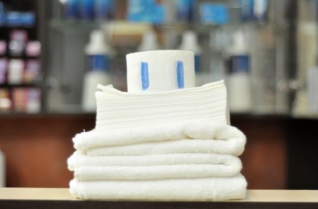 美容院用の白い清潔な綿タオル、使い捨てのペーパータオル、美容院での美容のための粘着テープ付き保護紙の首輪。