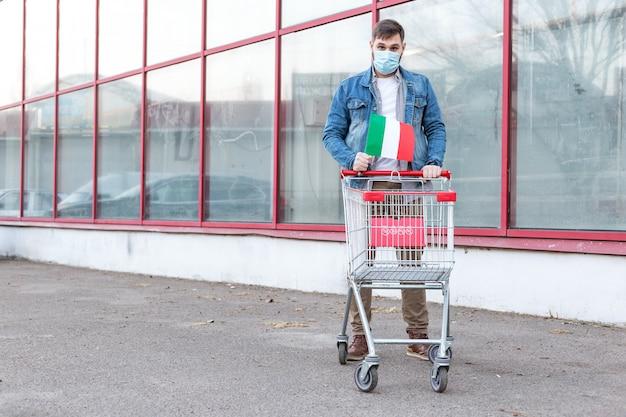 イタリアの旗と空のスーパーマーケットのトロリーと医療用防護マスクの男。食べ物を買うパニック。イタリアのコロナウイルス感染症の蔓延。