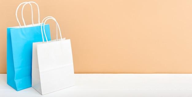 Белые синие крафт бумажные пакеты. покупки макет сумки бумажные пакеты на белом столе бежевый светлый фон с копией пространства.