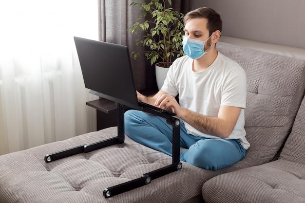 ノートパソコンとインターネットを使用して自宅から防護マスクを身に着けている若い白人男性。居心地の良いホームオフィス、リモートワーク、フリーランサー。