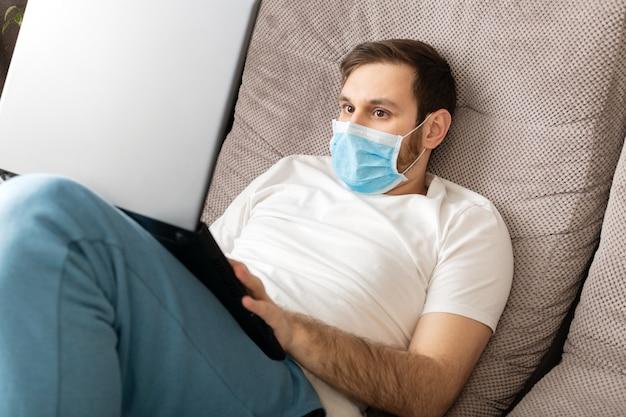 ノートパソコンとインターネットを使用して自宅から防護マスクを身に着けている若い白人男性。リモートワーク、フリーランサー。