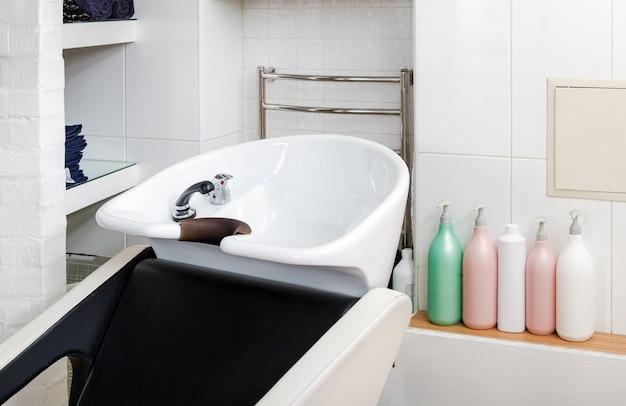 理髪ボウル、洗髪機。ビューティーサロンインテリア。ビューティーサロンや理髪店で髪を洗うための洗髪シンク。美容師のスタイリストの作業スペース。