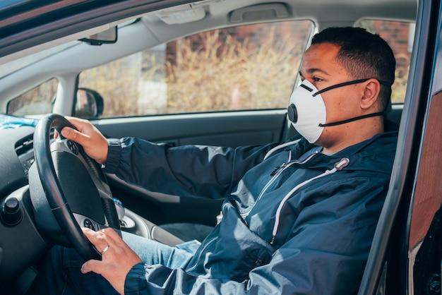 Молодой латиноамериканец в машине носит защитную маску для предотвращения распространения коронавируса.