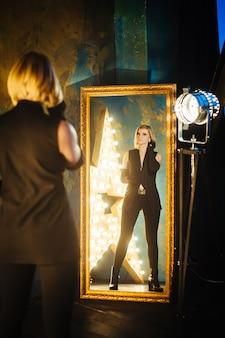 黒い服と手袋のランプが付いている星の背景に鏡にとどまっている金髪の若い女性