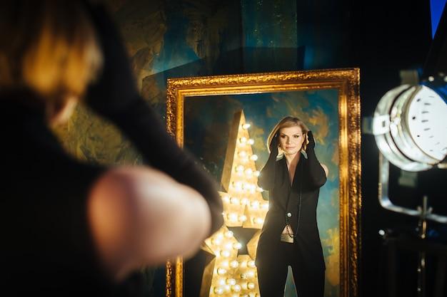 黒い服と手袋の星の背景の鏡にとどまって髪に触れる美しい金髪の若い女性。