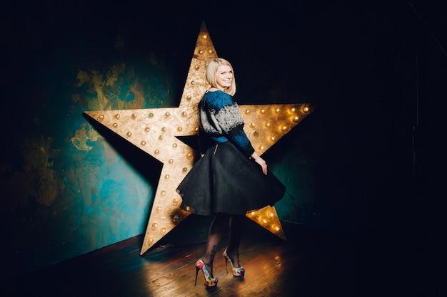 星の背景に黒のダンスで美しい金髪の若い女性。