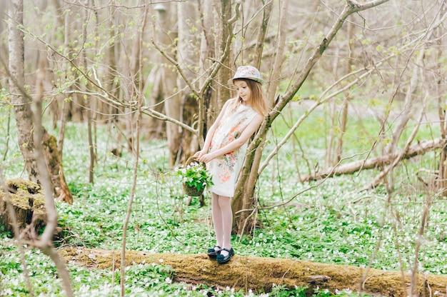 白いドレスを着た美しい少女は、春の森を歩きます。帽子のかわいい女の子とスノードロップのバスケットの肖像画。