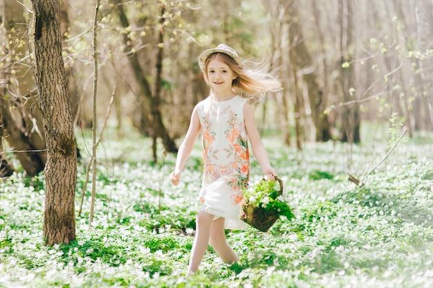 森の中を走る白いドレスを着た美しい少女。彼女の頭に帽子とスノードロップのバスケットを持つかわいい女の子の肖像画。