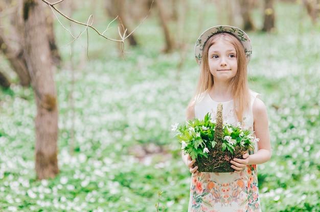 春の森の白いドレスを着た美しいブロンドの女の子。彼女の頭に帽子とスノードロップバスケットのかわいい女の子の肖像画