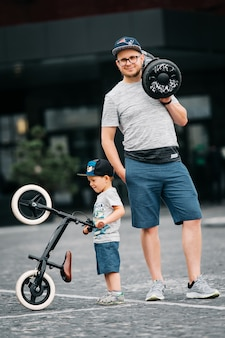 息子と父親は楽しく活発に活動しています。セグウェイとランバイクに乗っています。スタイリッシュな家族。