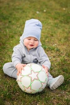 夏の散歩、自然の少年。スポーツ家族。少年はボールでサッカーをします。