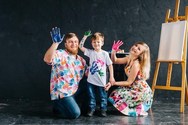 鮮やかなカラーライフ。絵画と楽しい子供たちと幸せな親の肖像画。彼らは明るい色で描かれた自分の手を示しています。私たちは家にいて、楽しみながら絵を描きます。