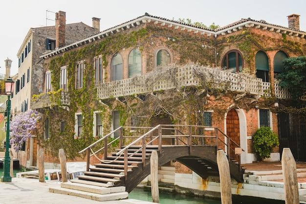ベニスのテラスと花のパティオ。ブドウの穴が生い茂ったファサードのある家。ヴェネツィアの運河に架かる橋。