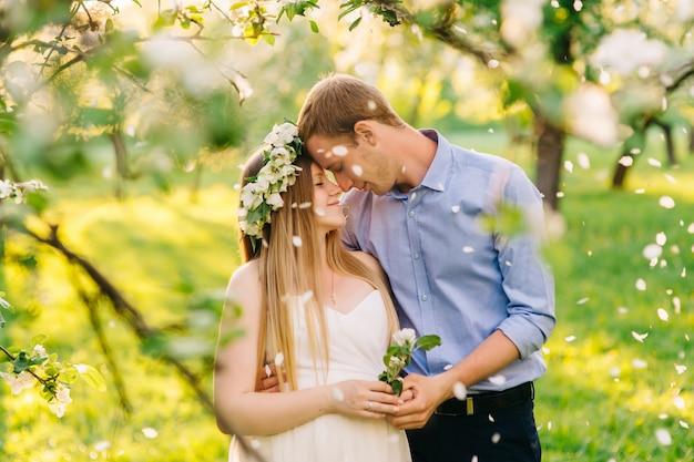 白いドレスを着た妊娠中の女性と彼女の頭に花のリースが庭で夫と一緒にいます。彼らは妊娠中の腹の花びらと手をつないで日光の下に落ちています。