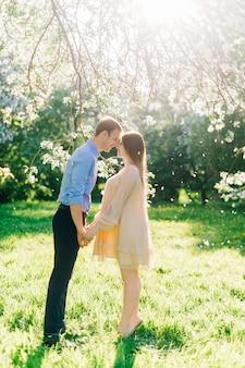 ブルーミングガーデンの美しい妊婦。彼らは妊娠中の腹と笑いながら手をつないでいます。太陽の下で花びらが降っています。