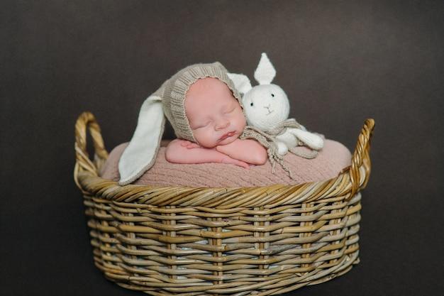 かわいい生まれたばかりの赤ちゃんは、ウサギの衣装を着た木製の背景にあります。イースターホリデー。