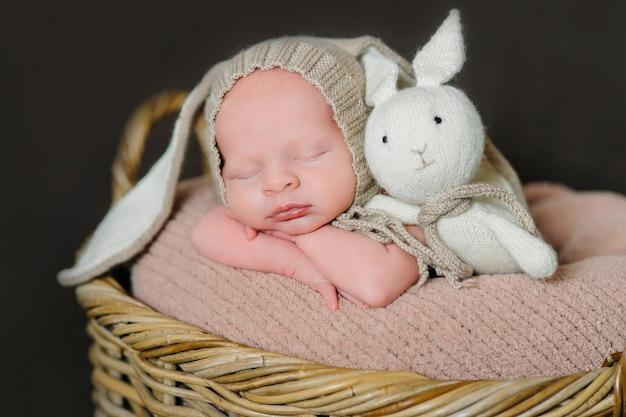 かわいい生まれたばかりの赤ちゃんは、ウサギの衣装を着た木製の背景にあります。イースターホリデー。素朴なスタイルの風景