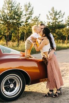 Ривьера в стиле ретро. уникальная машина. мальчик стоит на капоте ретро-автомобиля, и его родители целуют его
