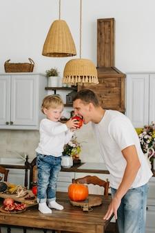 Отец и сын, вместе готовить на кухне. сын кормит папу тыквой.