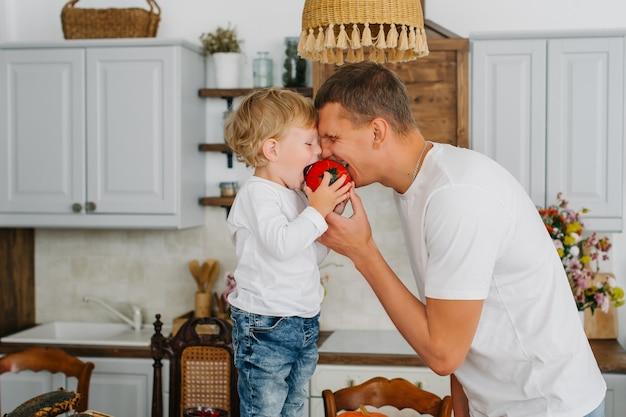 Отец и сын, вместе готовить в стильной кухне. сын и папа кусают вместе.