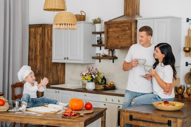 Выпечка праздник малыш сын концепции. родители пьют чай, в то время как маленький милый мальчик играет с мукой в красивой внутренней кухне.